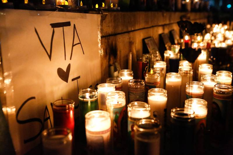 """A nighttime shot of dozens of glassed-in candles lining a low wall alongside a sign that reads, """"VTA [heart] San Jose."""""""