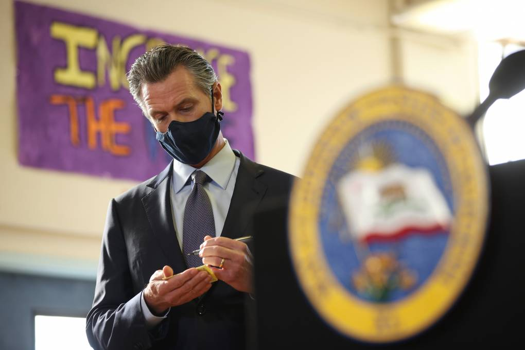 Gavin Newsom, wearing a black mask and standing beyond a podium with the Seal of California, scribbles in a tiny notepad.