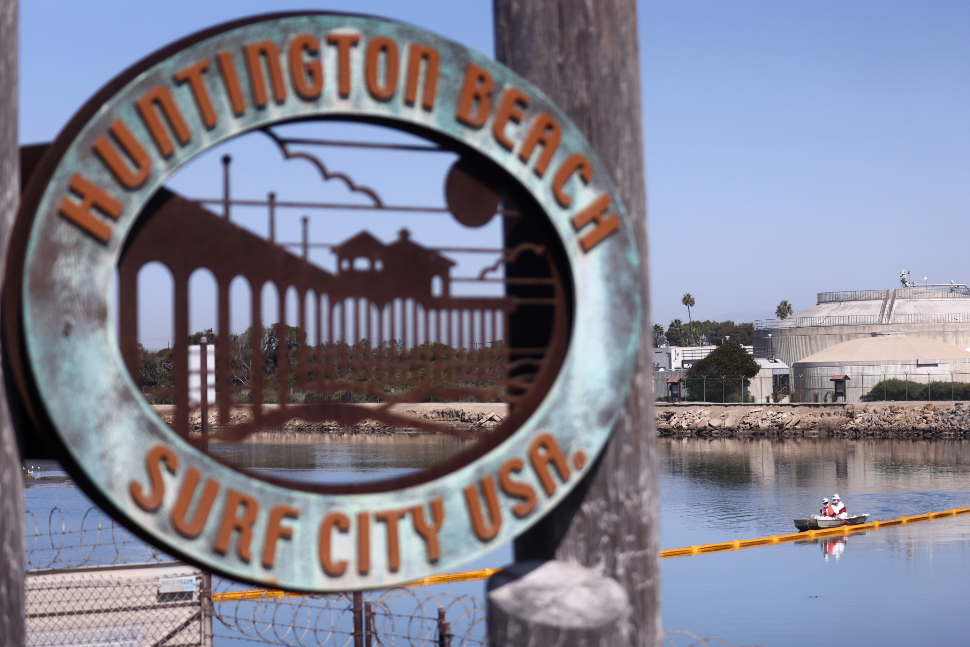 """A close-up of a sign saying """"Huntington Beach, Surf City USA"""" with water in the background, and a small boat on the water with two people inside."""
