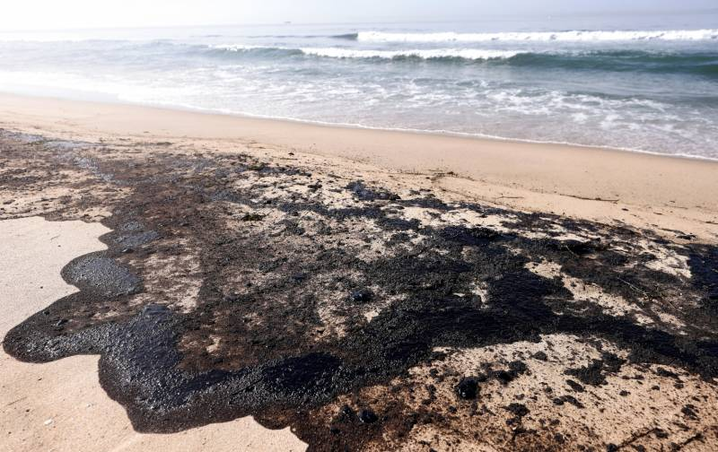 A giant black pool of oil washes up on a beach. Waves are seen in the background.