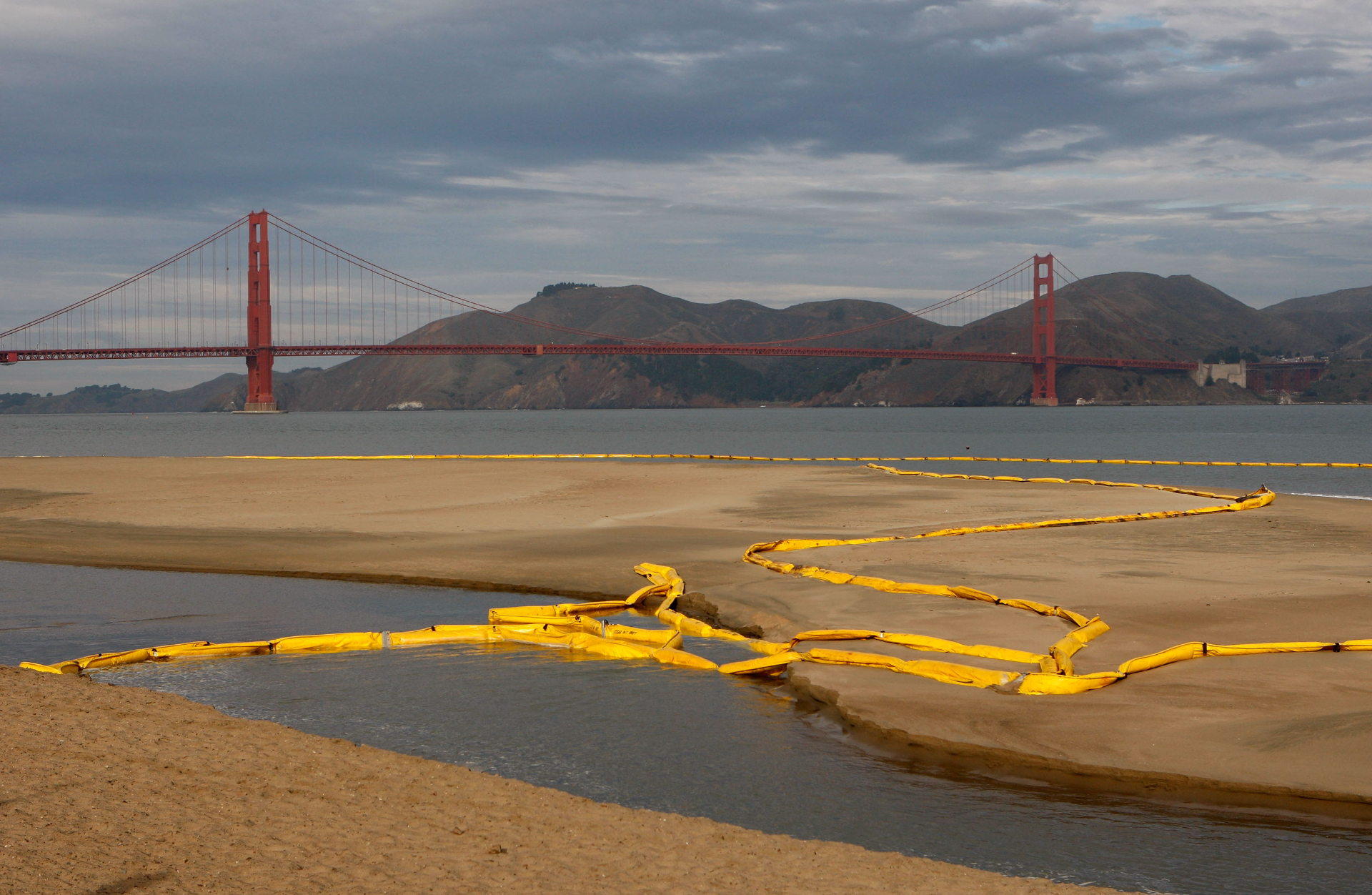 Long yellow inflatables, called booms, are coiled in the water and beach inside the Golden Gate Bridge.