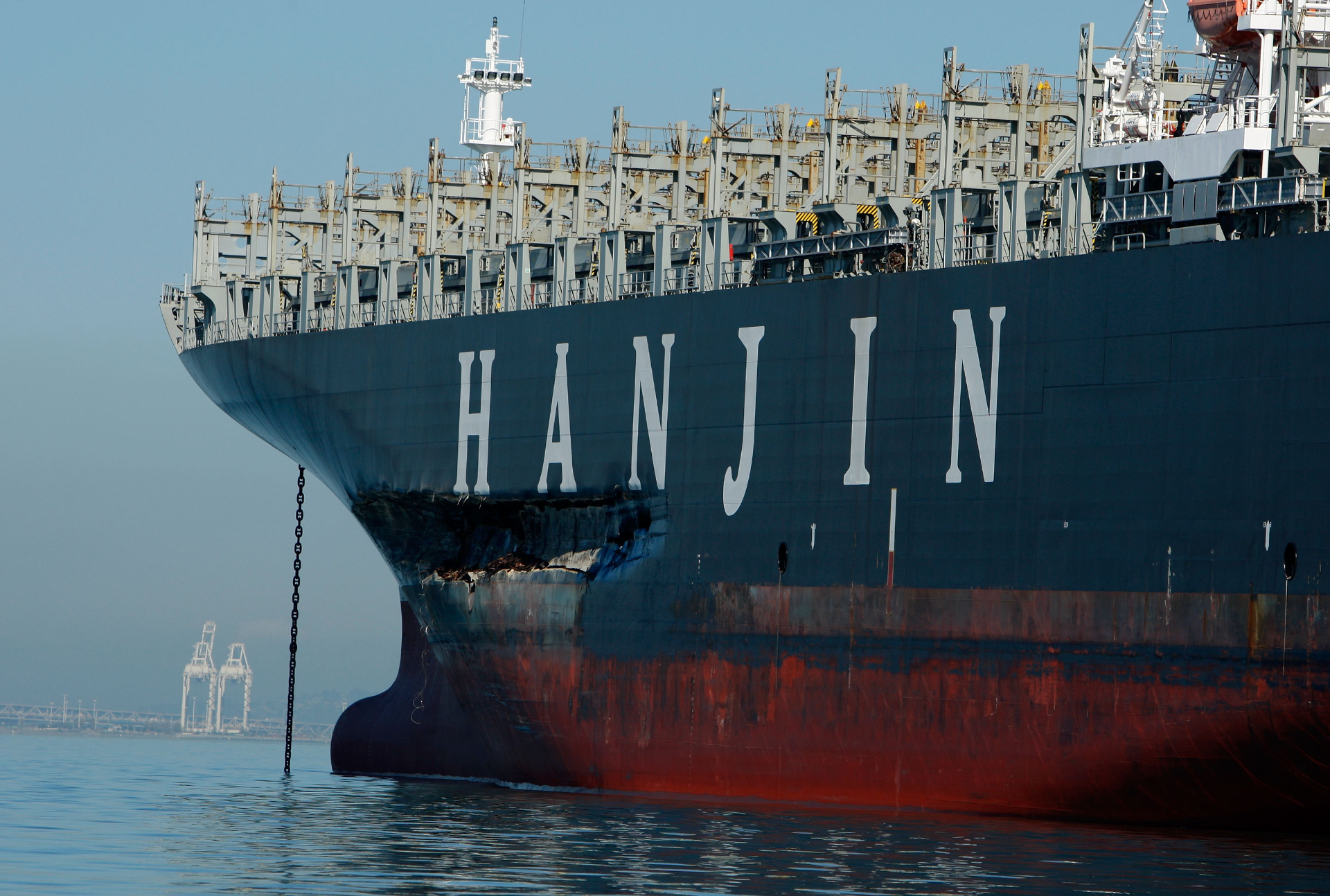 A large oil cargo ship sits in water with obvious damage to its hull.