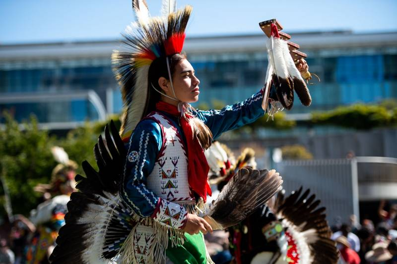 A dancer in a red, blue, and white costume, including a headdress and a feathered tail, holds feathers in both hands and faces the sun.