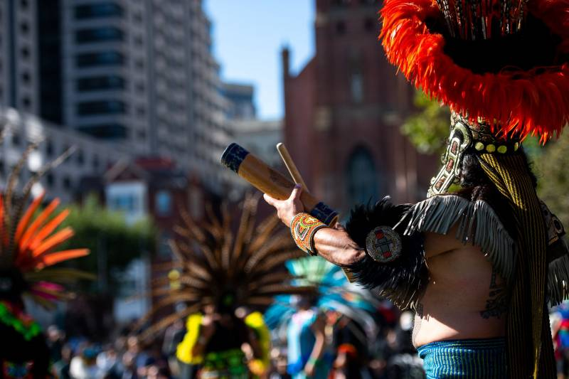 A close-up of hands holding a tubular wooden instrument and a drumstick, with an elaborate headdress in the background.