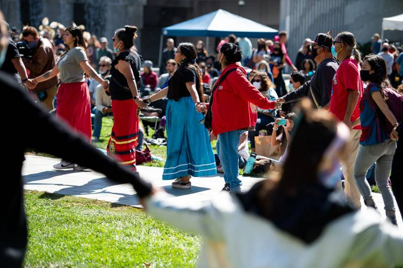 Several people dance holding hands in a circle, amid a crowd sitting on blankets on a lawn.