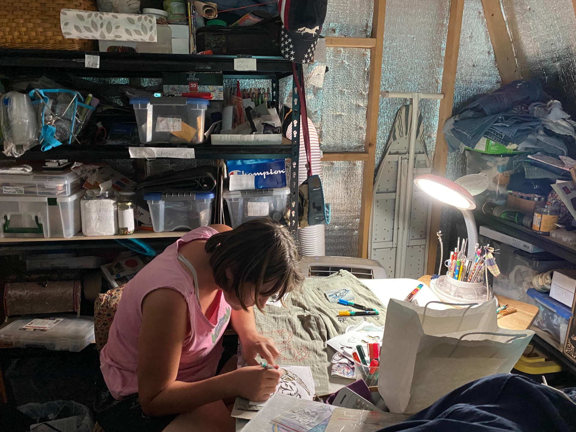A woman bends over some crafting work in a shed, with a lamp hovering over her work.