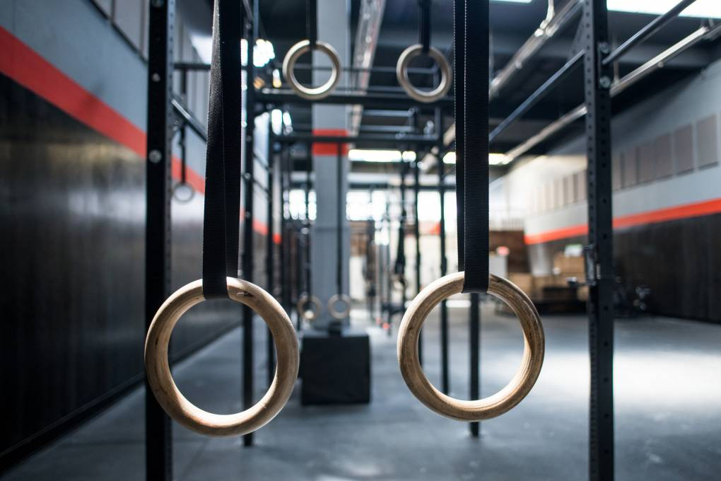 An image shows crossfit rings hanging with an empty gym in the background.