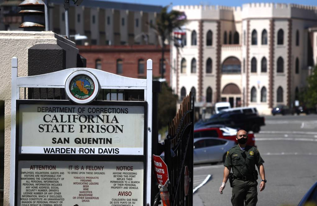 A guard stands next to the San Quentin prison gate