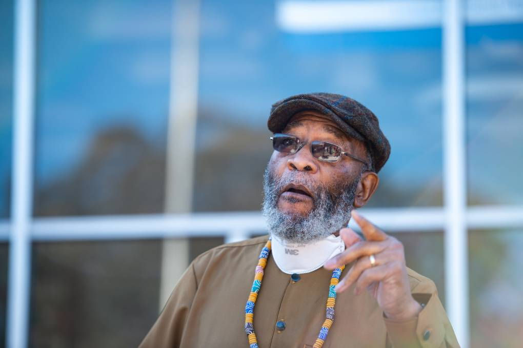 Amos Brown, in a hat, beard, glasses, and green, blue and yellow necklace, raises his hand mid-speech, the windows of a building behind him.