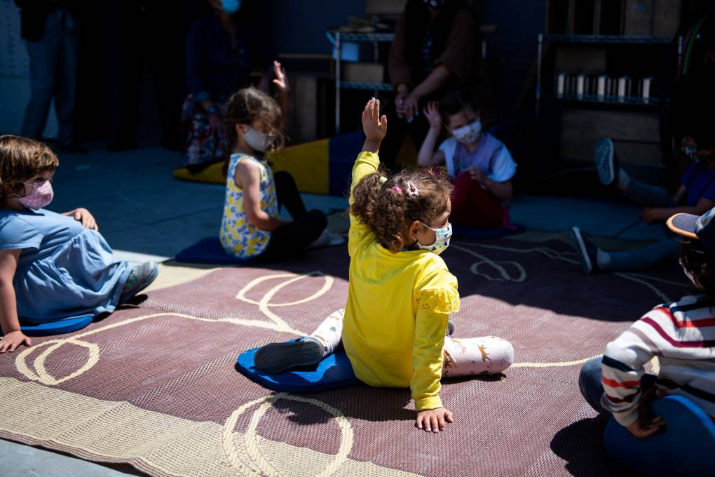 A little kid in a bright yellow sweater, sitting in the sun on a mat amid other little kids with their hands up, raises her hand.