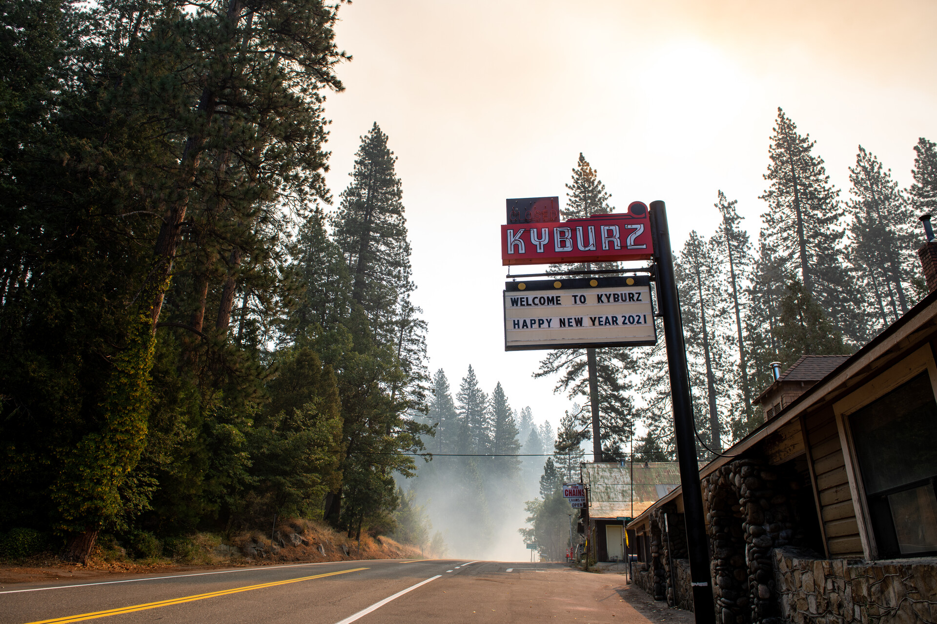 A red and white sign on a tall pole along a two-lane road, surrounded by tall fir trees, with smoke haze in the distance.