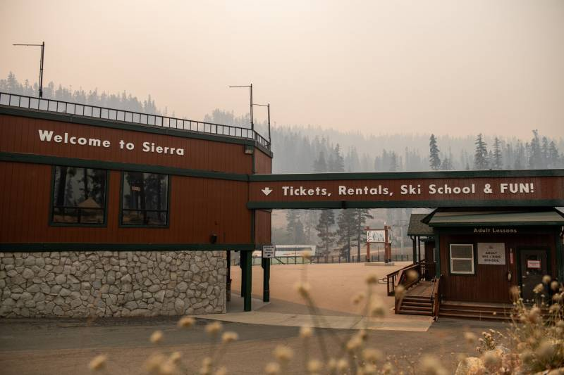 The front gates of a resort stand in front of a mountainous landscape covered in orange and gray smoke.