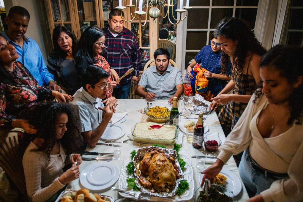 Family members stand around a table with many Thanksgiving dishes