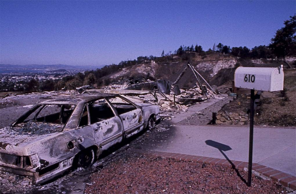 Grainy image shows a pristine mailbox with the address 610 overlooking a singed driveway that leads to a charred car with wildfire rubble and the ridge of the East Bay Hills in the distance.
