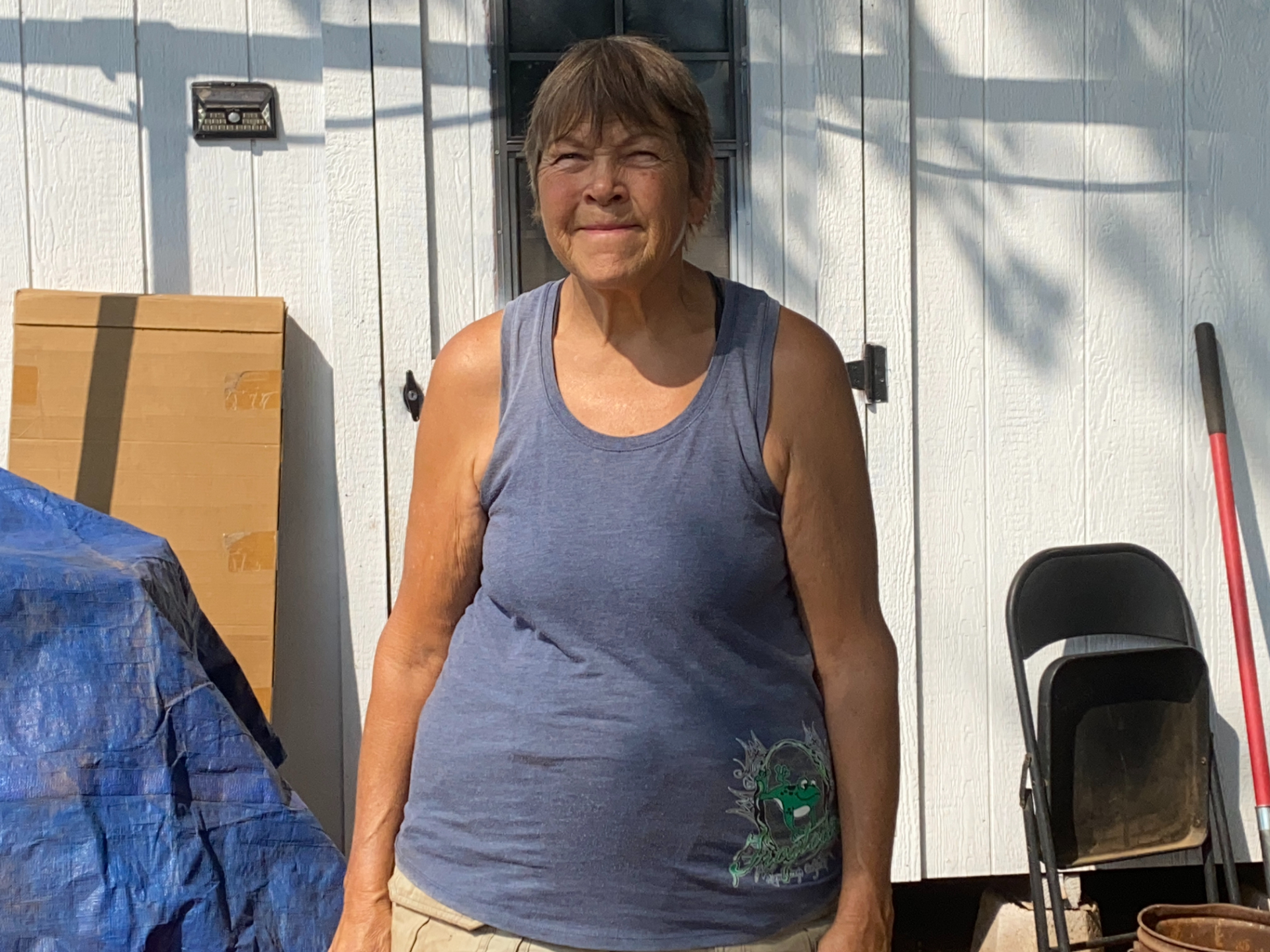 A woman in a tank top stands in front of a storage shed, with a slight smile and eyes closed in the bright sun.