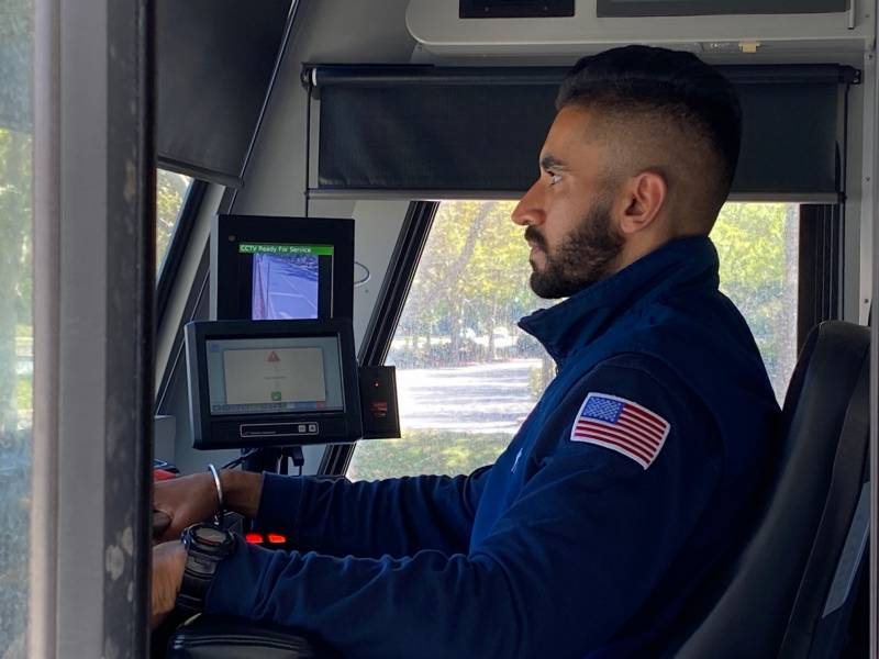 A man wearing a blue work jacket with an American flag patch on the left shoulder sits at the controls of a train, looking through the windshield.