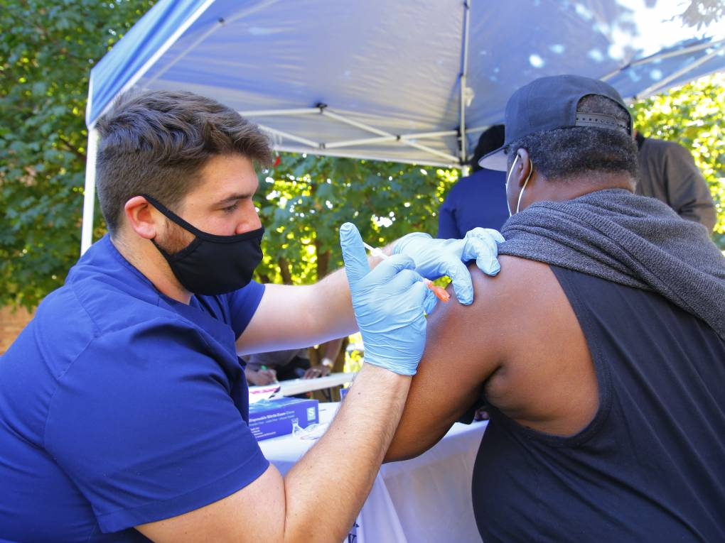 A man in blue scrubs, a mask, and blue gloves gives a man in a black T-shirt and baseball cap a shot in his upper arm beneath a tent outdoors amid trees.
