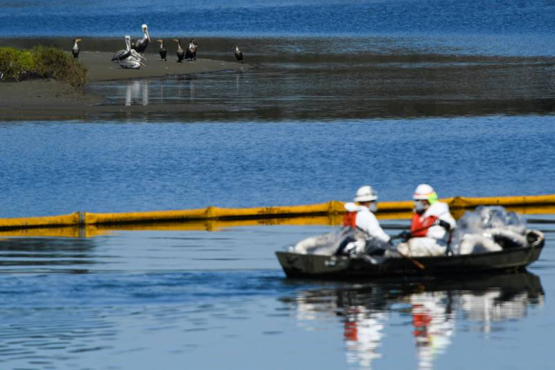 Two people in white protective gear and orange life vests float in a rowboat on oil-slicked water beyond a long yellow inflatable boom.