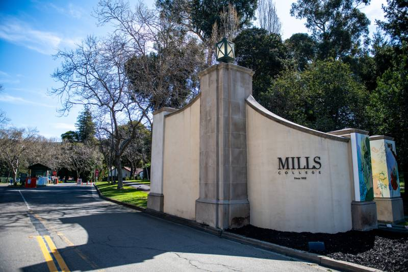"""The main entrance to the leafy Mills College campus, a rounded concrete wall with """"Mills"""" written on it."""