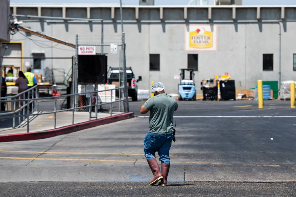 A man wearing a T-shirt, pants tucked into knee-high boots, and a hairnet walks across a parking lot toward a long, gray building.