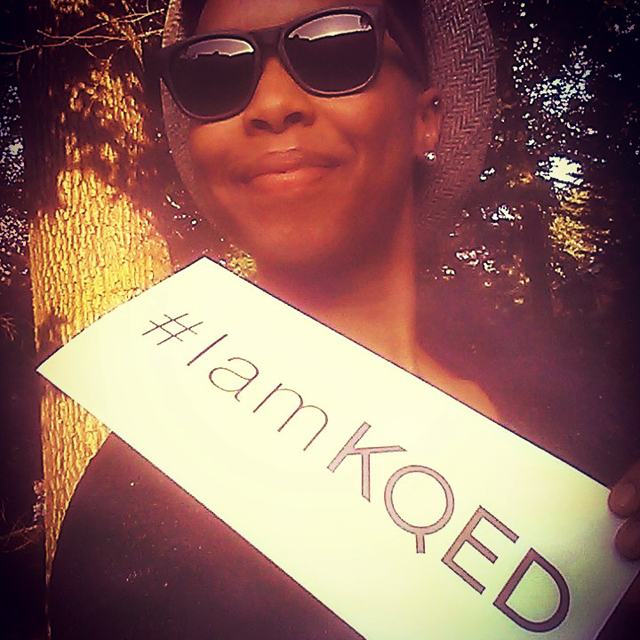 Carolyn Malachi and the #IamKQED sign. Photo courtesy of Carolyn Malachi.