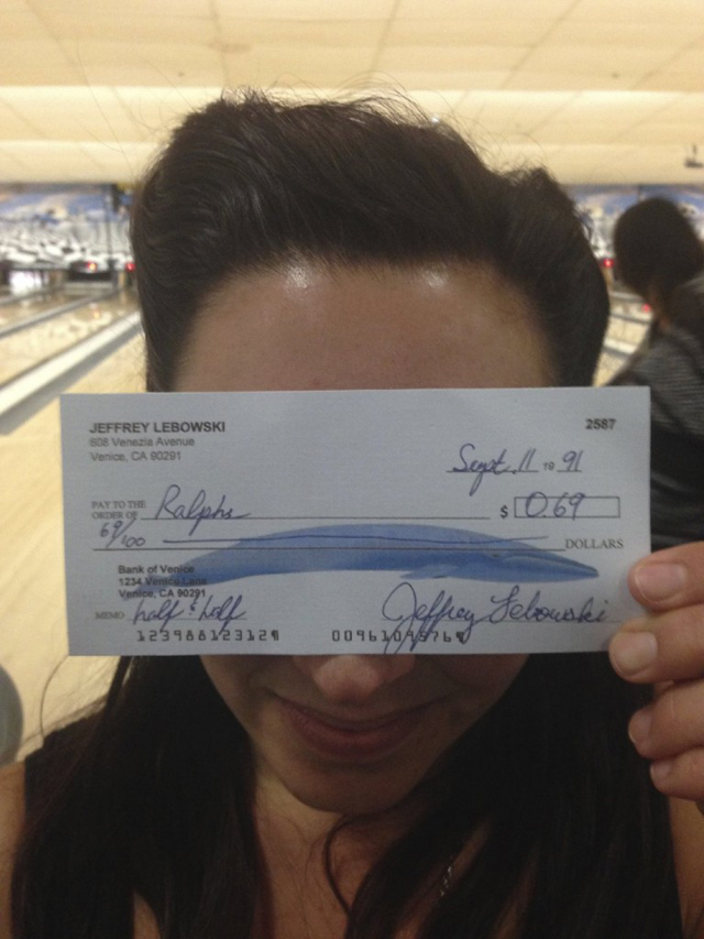 My friend holds up a check given to her by a Dude.