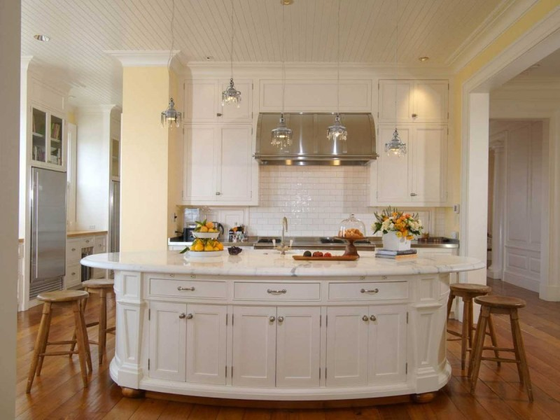 the-kitchen-has-a-large-island-and-shiny-light-fixtures
