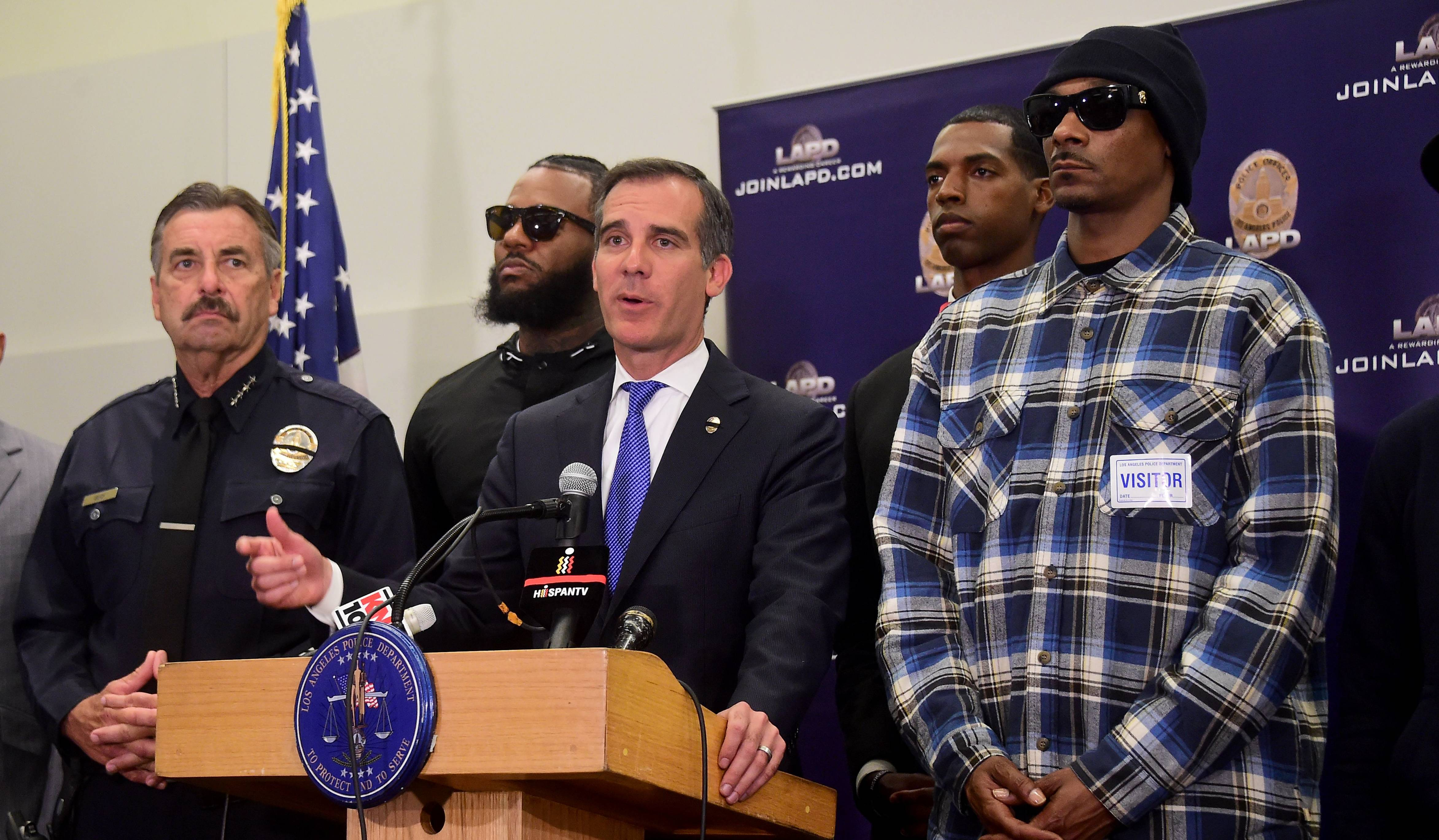 Los Angeles mayor Eric Garcetti addresses the media with police chief Charlie Beck (L) and rappers The Game (2/L) and Snoop Dogg (R) at LAPD headquarters on July 8, 2016, after Snoop Dogg and fellow rapper The Game led a peaceful demonstration outside a Los Angeles Police Department recruit graduation ceremony in what they called an effort to promote unity in the aftermath of the deadly shootings of police officers in Dallas.