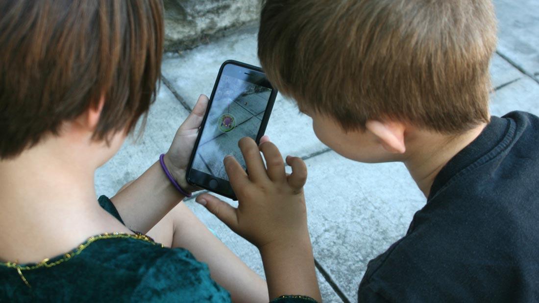 Two kids try to capture a Pokémon in Pokémon Go.