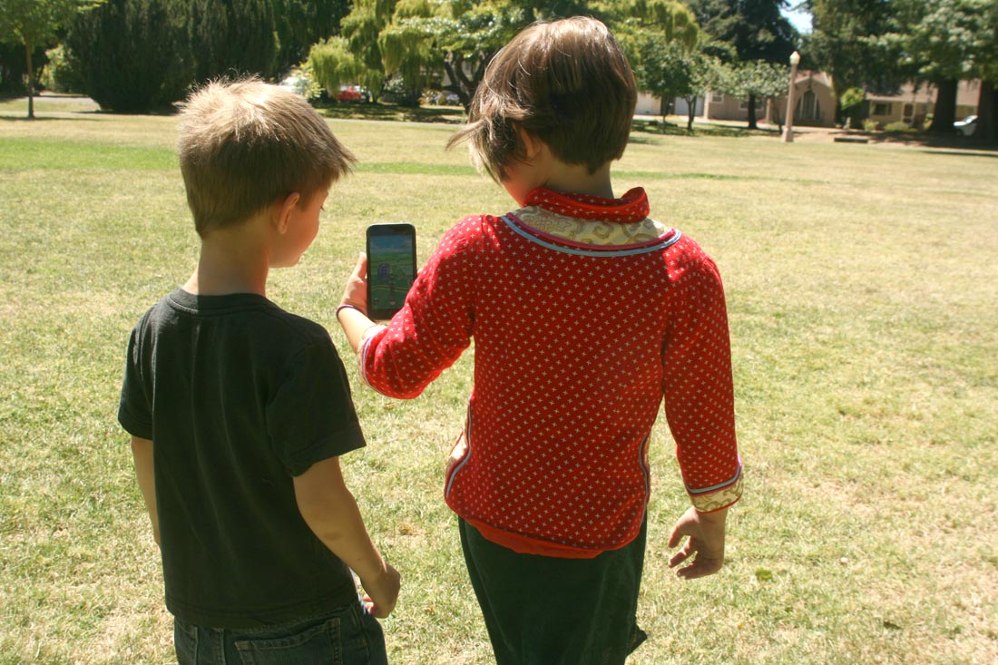 Two kids play Pokémon Go in the park. Note the absence of other players. That would soon change.