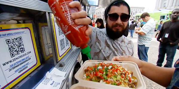 Spotted in the wild, a bearded millennial adds his millennial hot sauce of choice to a dish served out of a millennial-friendly truck.