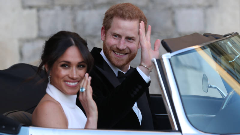 Meghan Markle, the Duchess of Sussex, and Prince Harry wave as they leave Windsor Castle en route to their post-wedding reception.