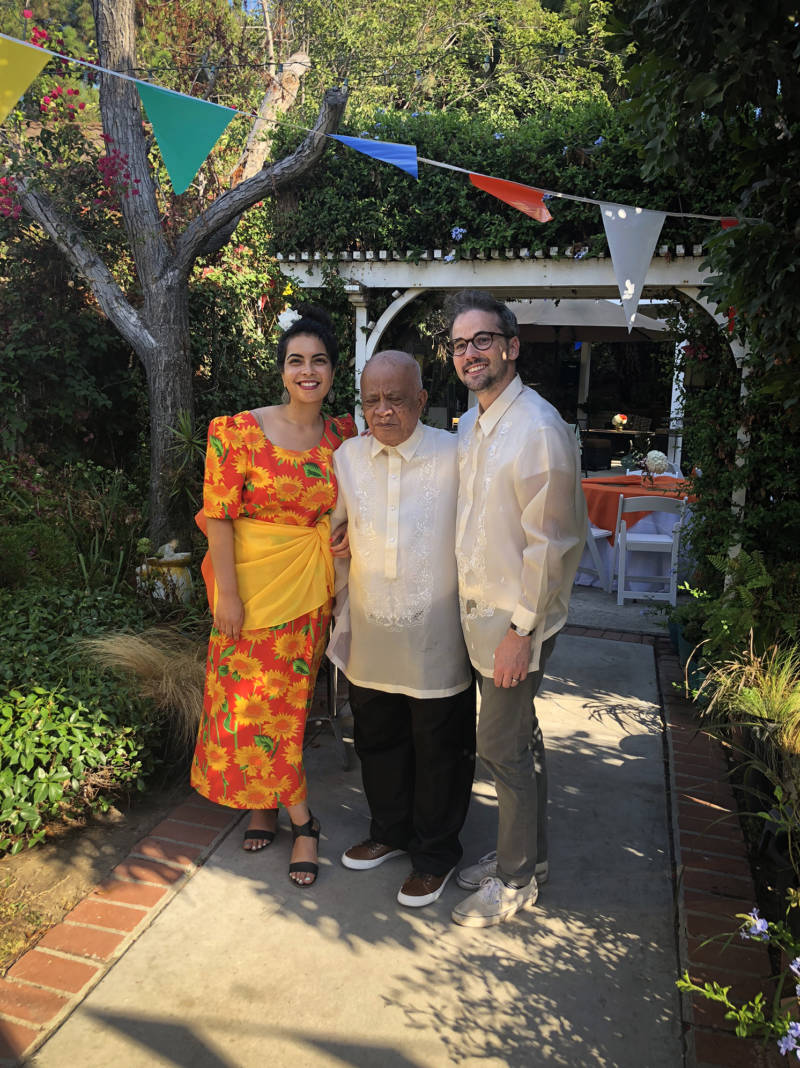 Malaka Gharib, her grandfather Floro Mercene and her husband, Darren Vandergriff, wear traditional Filipino clothing at her grandfather's birthday party.