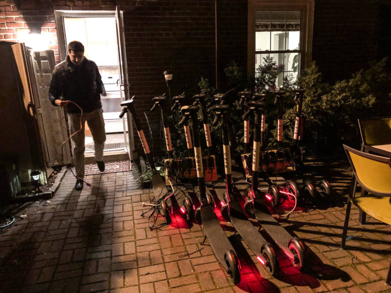 Joel Kirzner charges Bird scooters on his patio in Arlington, Va., on March 4. He routinely picks up scooters after his workday is finished and charges them overnight for the companies Bird and Lime.
