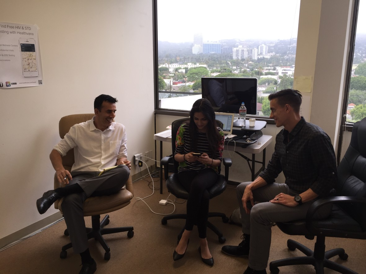 CEO Ramin Bastani, looking at Healthvana app, with Operations Associate Ishani Winston and COO Sean Crockett, in the company's Los Angeles office. (Adil Chamakh/Healthvana)