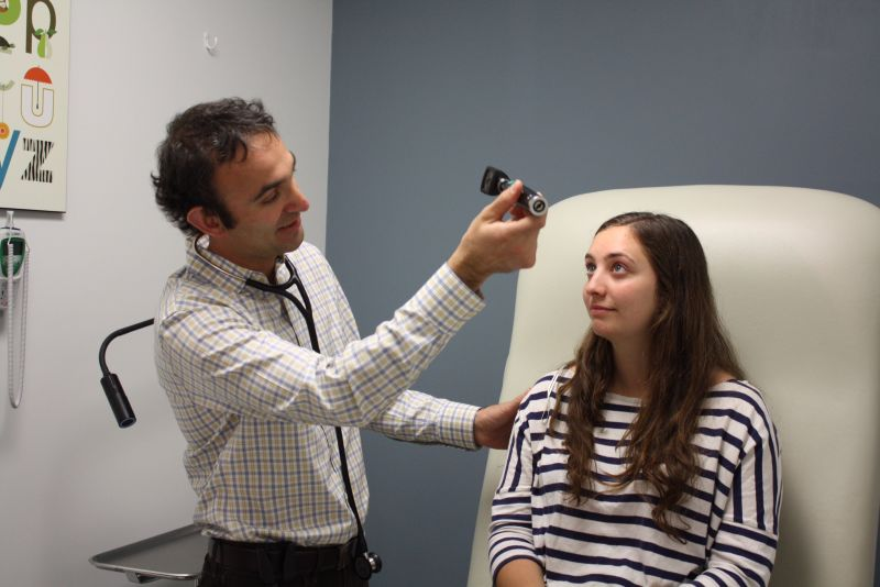 Physician and Direct Urgent Care President completes a pupillary exam during a routine physical check-up.
