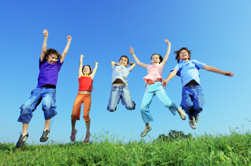 Five happy children jump in a meadow. Can wearable fitness trackers help motivate kids to get out and move?