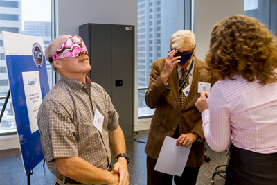 Commander Ken Bowersox (left) tries on a LumosTech mask at NSBRI headquarters in Houston.
