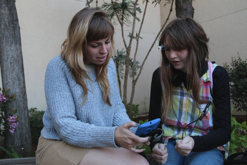 Study manager Beth McCarthy shows study participant Gabby Warner new features on the smartphone app that connects to Google Glass.