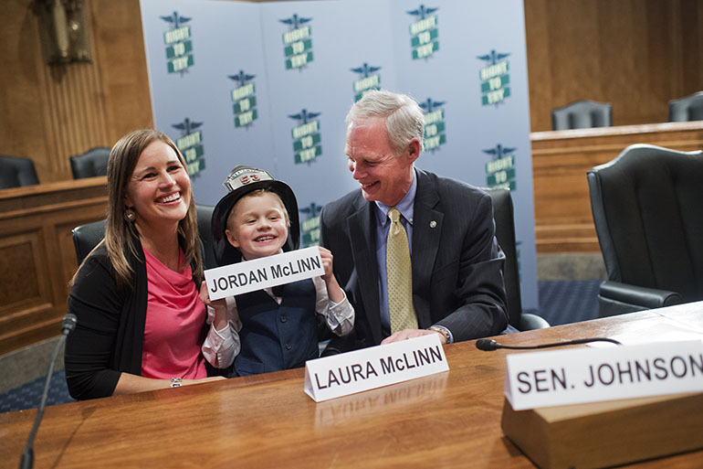 From left, Laura McLinn, of Indianapolis, her son Jordan, 7, and Sen. Ron Johnson, R-Wis., pose for a picture.