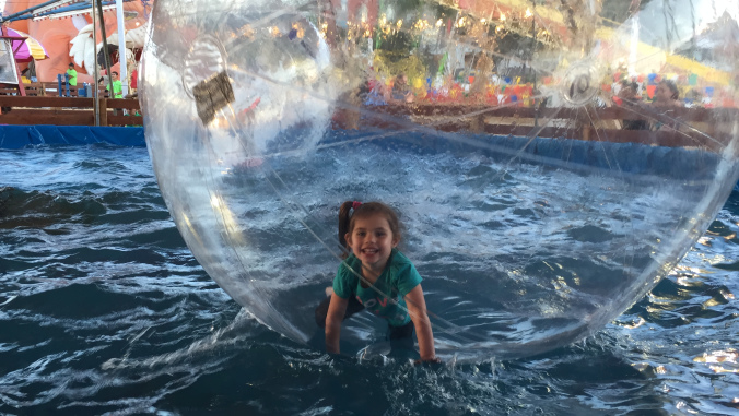 A little girl playing in a large plastic bubble on top of a pool.