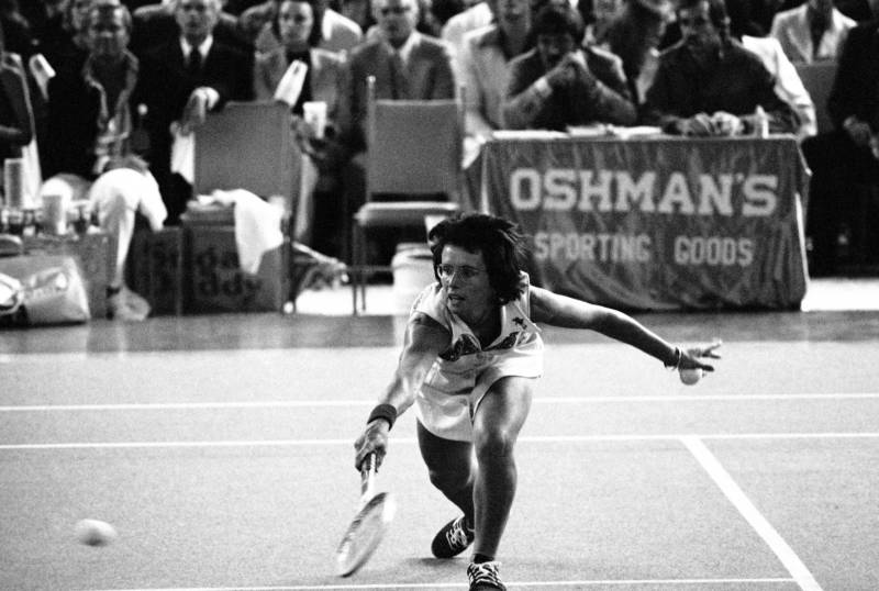 "Billie Jean King bends down low to send the ball back over the net during the match with Bobby Riggs in the Astrodome in Houston, Texas on Sept. 20, 1973. (""American Masters: Billie Jean King"")"