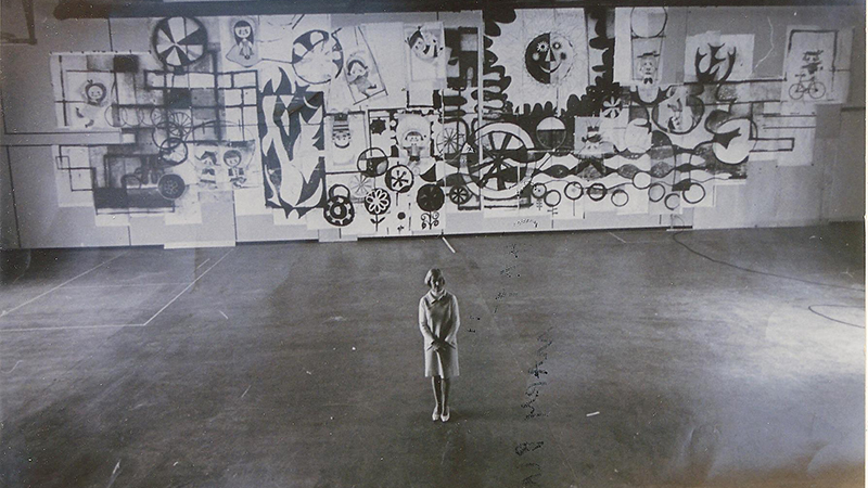 Mary Blair stands before her Tomorrowland mural design