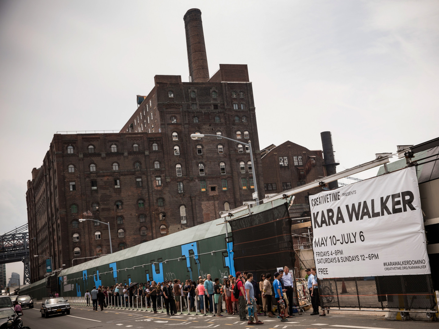 "Visitors wait in line for the Kara Walker exhibit on May 10, opening day. The show was housed in a former Domino Sugar refinery. Inside, visitors described the building as ""cathedral-like"" and ""creepy,"" and said it smelled like a bakery"