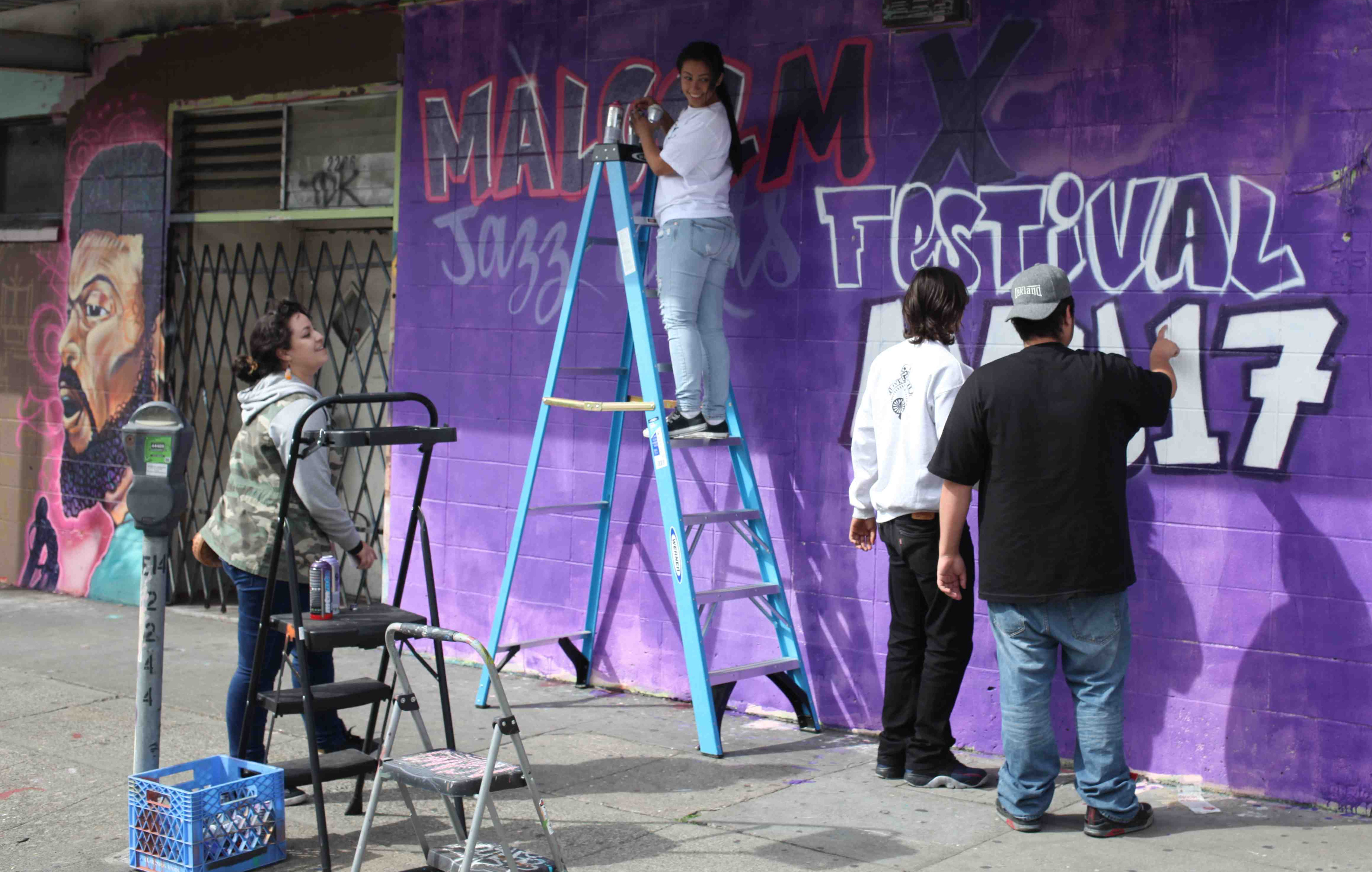 Eastside Arts Alliance members paint a festival announcement.