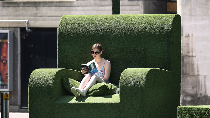 woman reading on giant chair made out of astroturf
