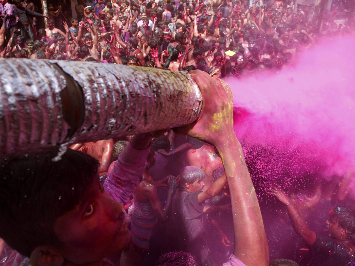 A man sprays colored dye on people dancing during Holi celebrations in India in 2012. Holi, the Hindu festival of colors, also heralds the coming of spring -- a detail that partiers at the Shout Color Throw might miss.