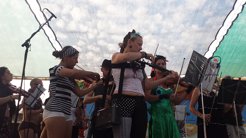 Madelaine Ripley and other violinists with the PlayaPops Symphony, the first-ever string orchestra at Burning Man, warm up before their performance at Center Camp