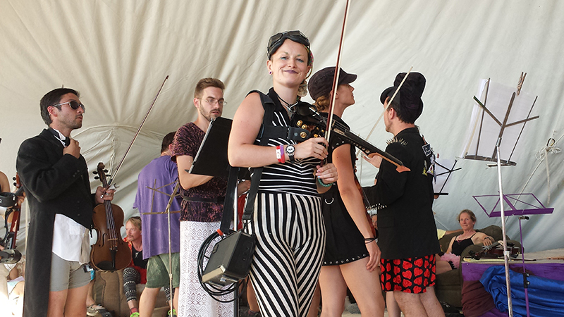 First chair Madelaine Ripley (black and white stripes) and other violinists with the PlayaPops Symphony prepare for their debut performance at Burning Man this year (2014