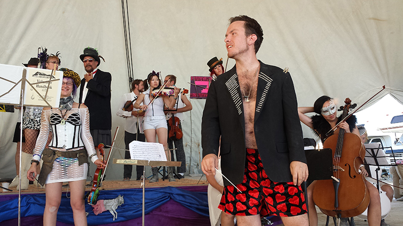 Eric Yttri, aka Dr. FireTuba, walks on stage to conduct the debut concert of the PlayaPops Symphony, the first-ever string orchestra at Burning Man.